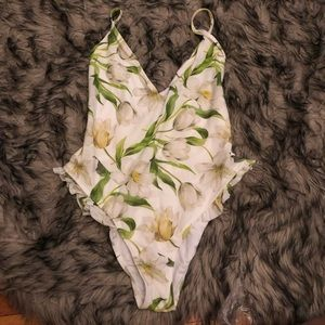 White swimsuit with green flowers and ruffles